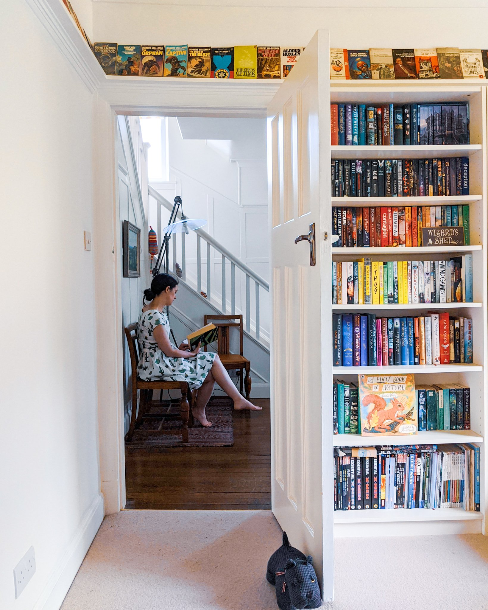 Woman reading a book through a library doorway to illustrate bookstagram post ideas.
