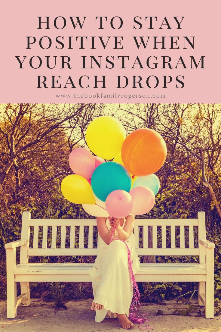 A woman hiding behind balloons symbolising staying positive after a drop in Instagram reach