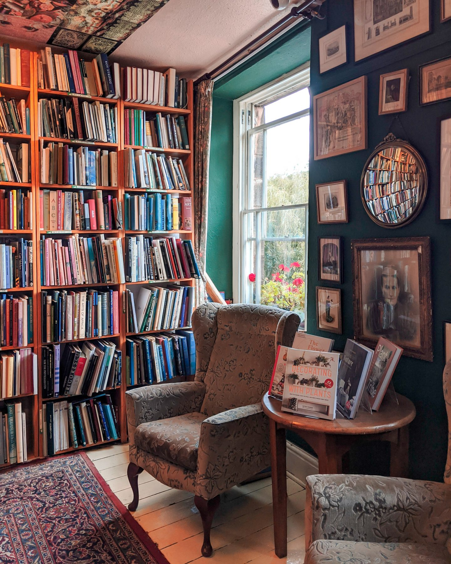 An armchair next to a table of books providing a cosy reading retreat.