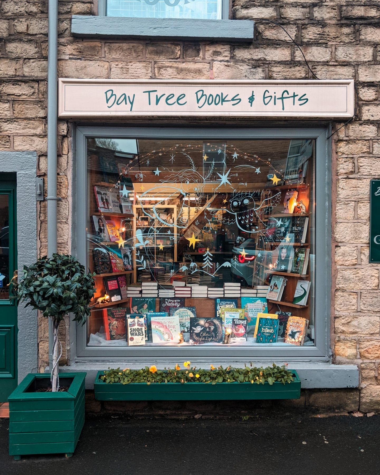 The shop window of Bay Tree Books in Glossop, Derbyshire. There is a Bay Tree in a pot outside.