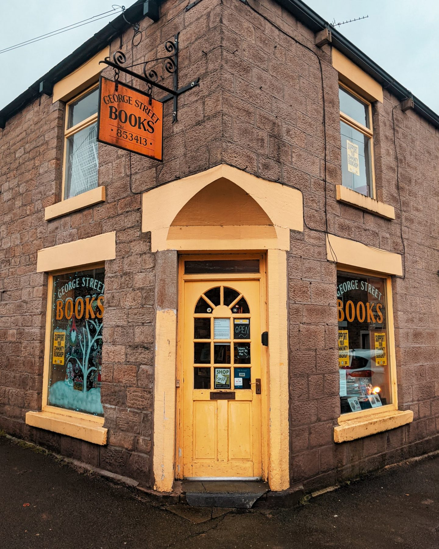 The front entrance of George Street Community Bookshop in Glossop. The building has a yellow front door and yellow window frames.