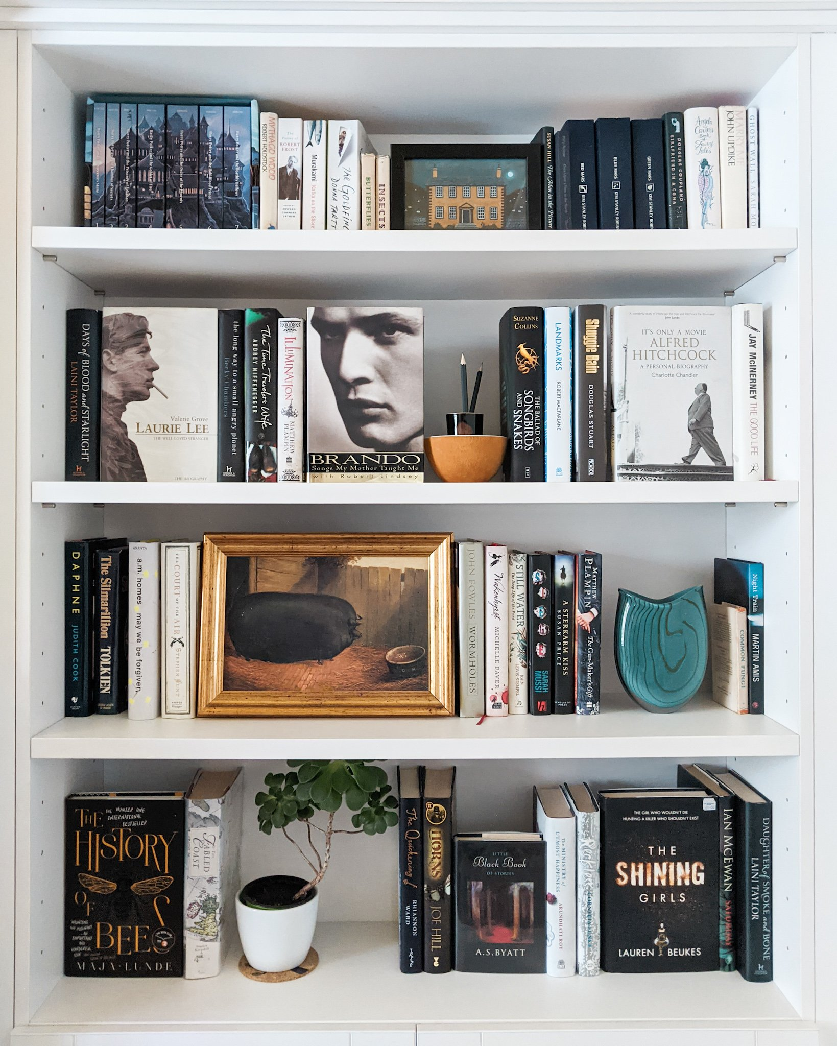 A bookshelf shelving ideas showing black and white books mixed with prints and plants
